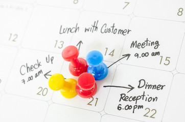 Pushpin on calendar with busy day.