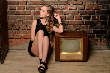 young sensual woman sitting near retro tv set