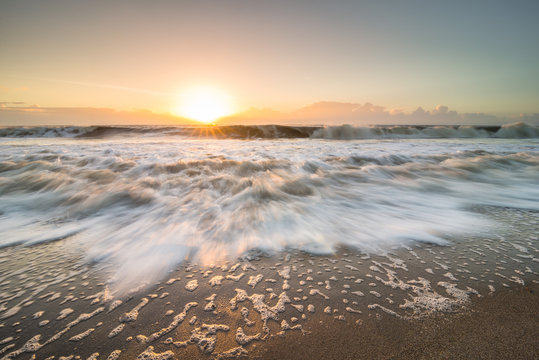 The rising tide rushing in towards land on Edisto Island, South Carolina during the sunrise.