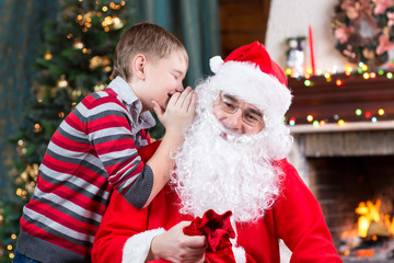 Santa Claus and child boy. Kid telling his Christmas wish in Santa Claus near the Christmas tree opposite fireplace
