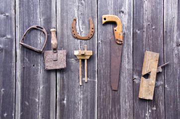Old rusty tools hanging on grey wooden wall