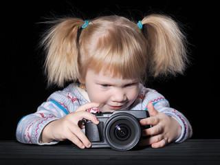 Маленькая девочка фотографирует. Ребенок держит фотоаппарат. Фон черный. Стол темная доска. Девочка блондинка со смешными хвостиками. Ребенку интересно