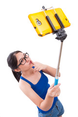 Happy woman taking picture with smartphone selfie stick