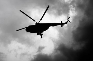 Garden Poster Helicopter silhouette of a helicopter in the clouds, black and white