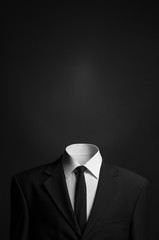 Surrealism and business theme: a man without a head in a black suit on a dark background in the studio