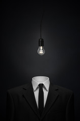 Surrealism and business theme: Burning glass bulb instead of a head man in a black suit on a dark background in the studio