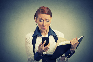 upset young business woman looking at phone seeing bad news holding book