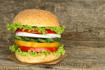 Healthy vegan burger with raw vegetables on old wooden background.