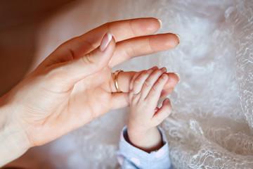 Newborn children's hand in mother hand. Mom and her Child. Happy