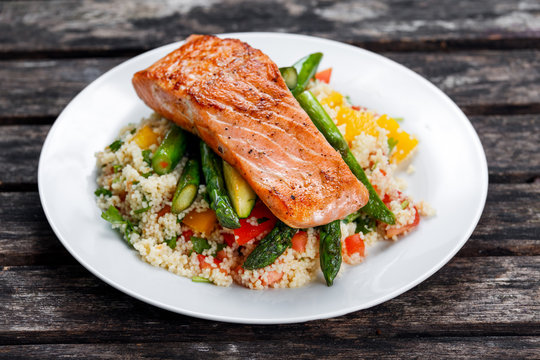 Pan fried salmon with tender asparagus and courgette served on couscous mixed with sweet tomato, yellow pepper salsa.