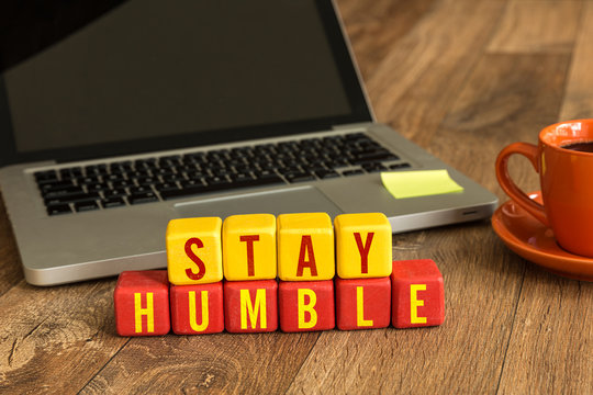 Stay Humble written on a wooden cube in a office desk