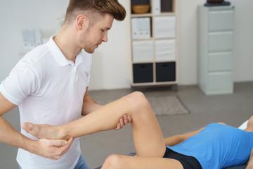 physiotherapeut behandelt eine patientin mit schmerzen am kniegelenk