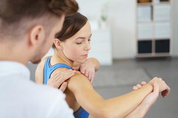 physiotherapeut behandelt eine patientin mit schmerzen an der schulter