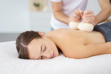 frau entspannt bei einer massage mit kräuterstempeln
