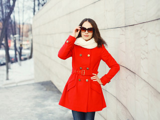 Pretty young woman wearing a red coat, sunglasses and scarf in c
