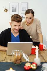 glückliches junges paar mit laptop in der weihnachtszeit