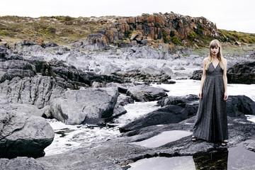 Beautiful woman in gray on rocky landscape, portrait