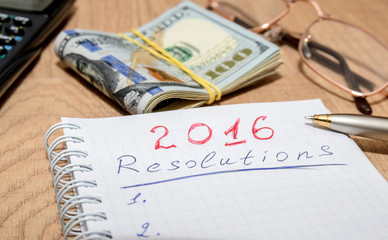 goals of year 2016 write on notebook with pen and dollars on wooden background