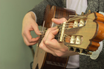 The fingers on the strings of a guitar playing
