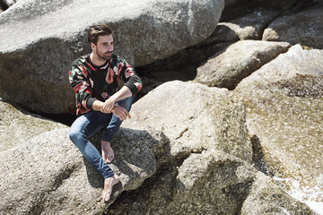 Young man sitting on rocks, looking away