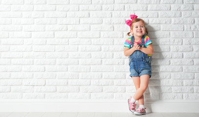 Happy child little girl laughing at blank brick wall