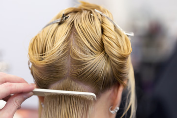 Hairdresser's hand making haircut for a blonde female client