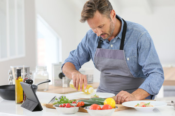 Man in kitchen cooking dish and using digital tablet