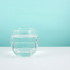 The medium glass of pure water on a white table.