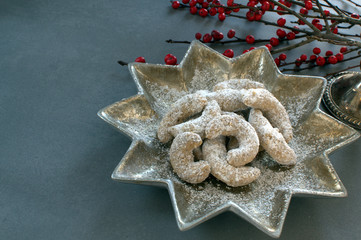 German Kipferl Cookies dusted with icing sugar on a star shaped plate against a grey background 1
