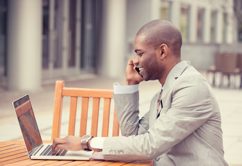 handsome young businessman working with laptop outdoors talking on mobile phone