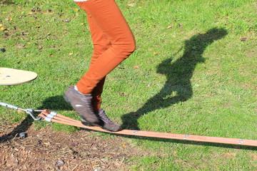 Schatten einer Frau beim Slacklinen in einem Park