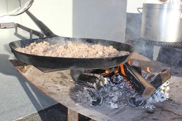 Ein Koch bereitet frischen Sterz (Heidensterz) über einem Lagerfeuer zu