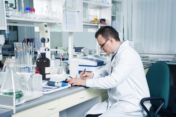 Scentist with pencil writing down observations in laboratory