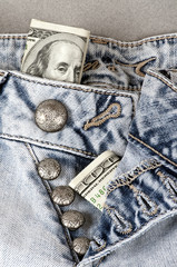 unbuttoned jeans with dollars sticking out, closeup