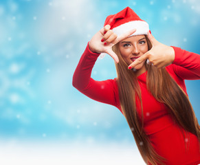 portrait of a beautiful young woman at Christmas doing a photo gesture