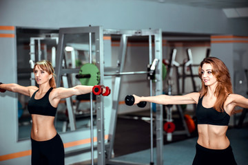 Two young girls workout in the gym