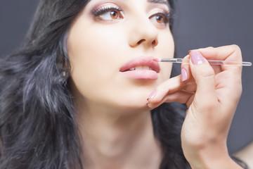 Closeup specialist in beauty salon gets lipstick, lip gloss, make-up.