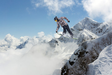 Flying snowboarder on mountains. Extreme sport.