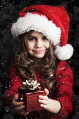 Fototapeta dziewczynka w czapce świętego mikołaja z prezentem obraz