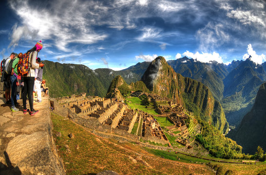 HDR image of tourists observing the wonder of Machu Picchu, the lost city of the Inca near Cusco, Peru.