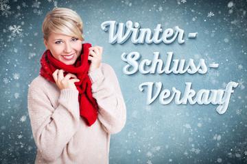 """junge blonde Frau mit Schal im Schneetreiben mit Wort """"Winterschlussverkauf"""""""
