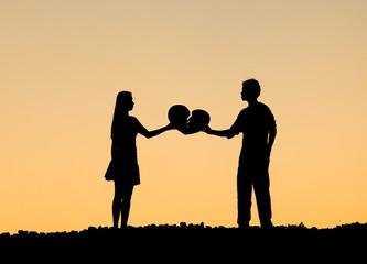A man and a woman holding a broken heart