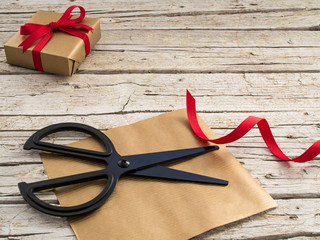 black scissor, gift and red ribbon on wooden background