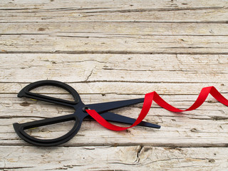 black scissor and red ribbon on wooden background