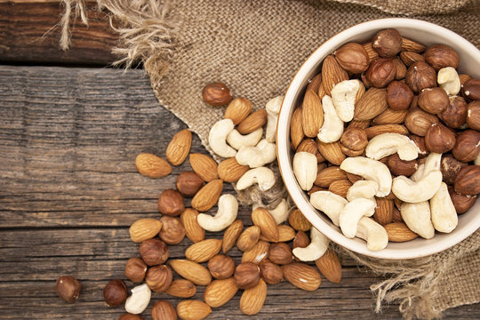 Almonds, cashew and hazelnuts in ceramic bowl on a rustic wooden