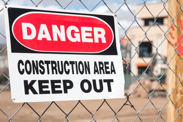 Danger Construction area sign hanging on a chain link fence at a construction site