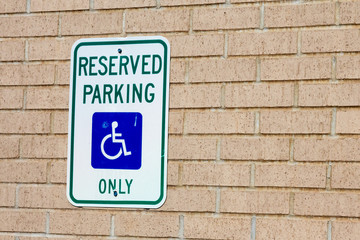 Reserved handicapped parking sign on the brick wall of a business