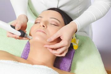 Woman having mesotherapy facial treatment at beauty salon. Close up