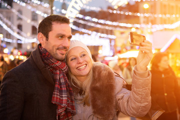 Young attractive couple in a christmas market taking selfie