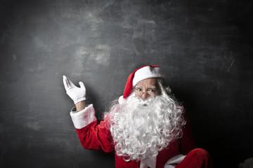 Santa Claus pointing at a blackboard